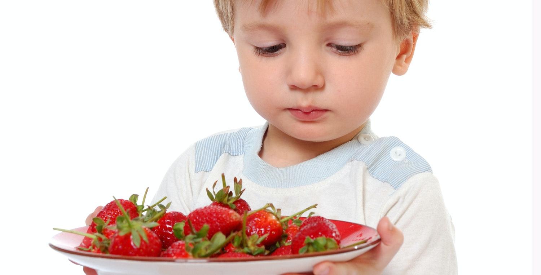 enfant avec un plat de fraises - image