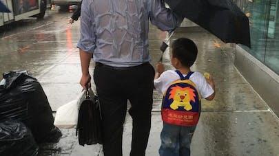 La photo d'un papa, tenant un parapluie pour protéger son   fils, fait le buzz