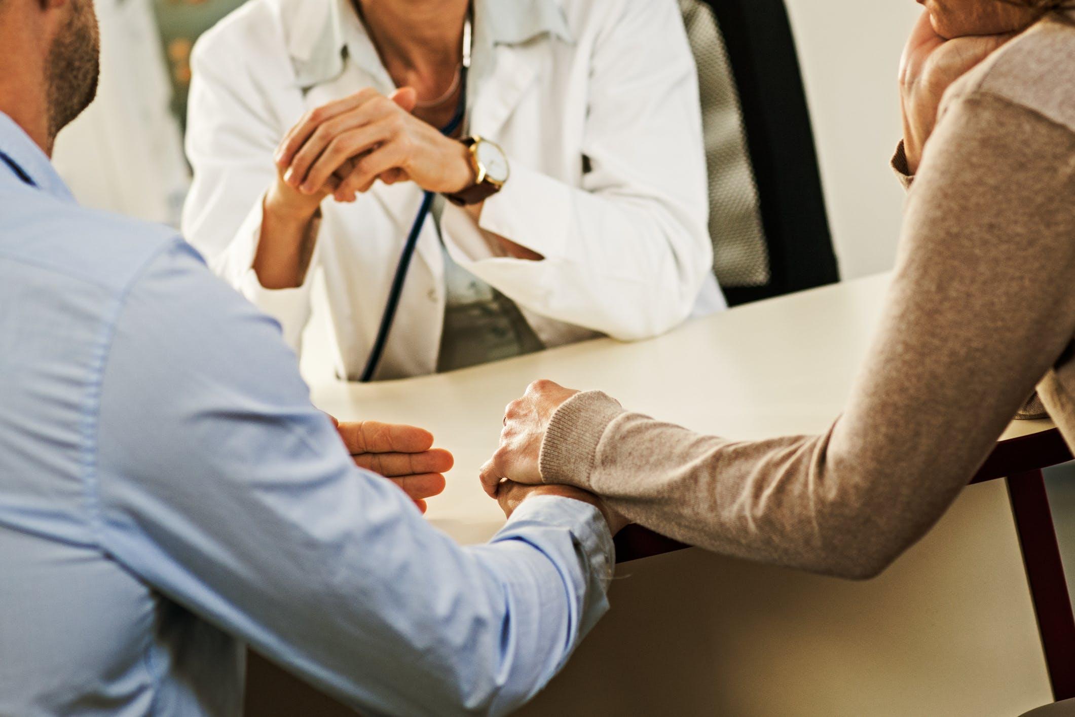 couple se tenant la main discute avec corps medical
