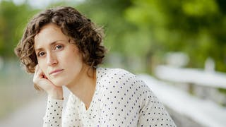 femme songeuse sur un banc
