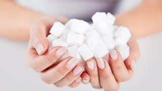 gros plan main remplie de morceaux de sucre