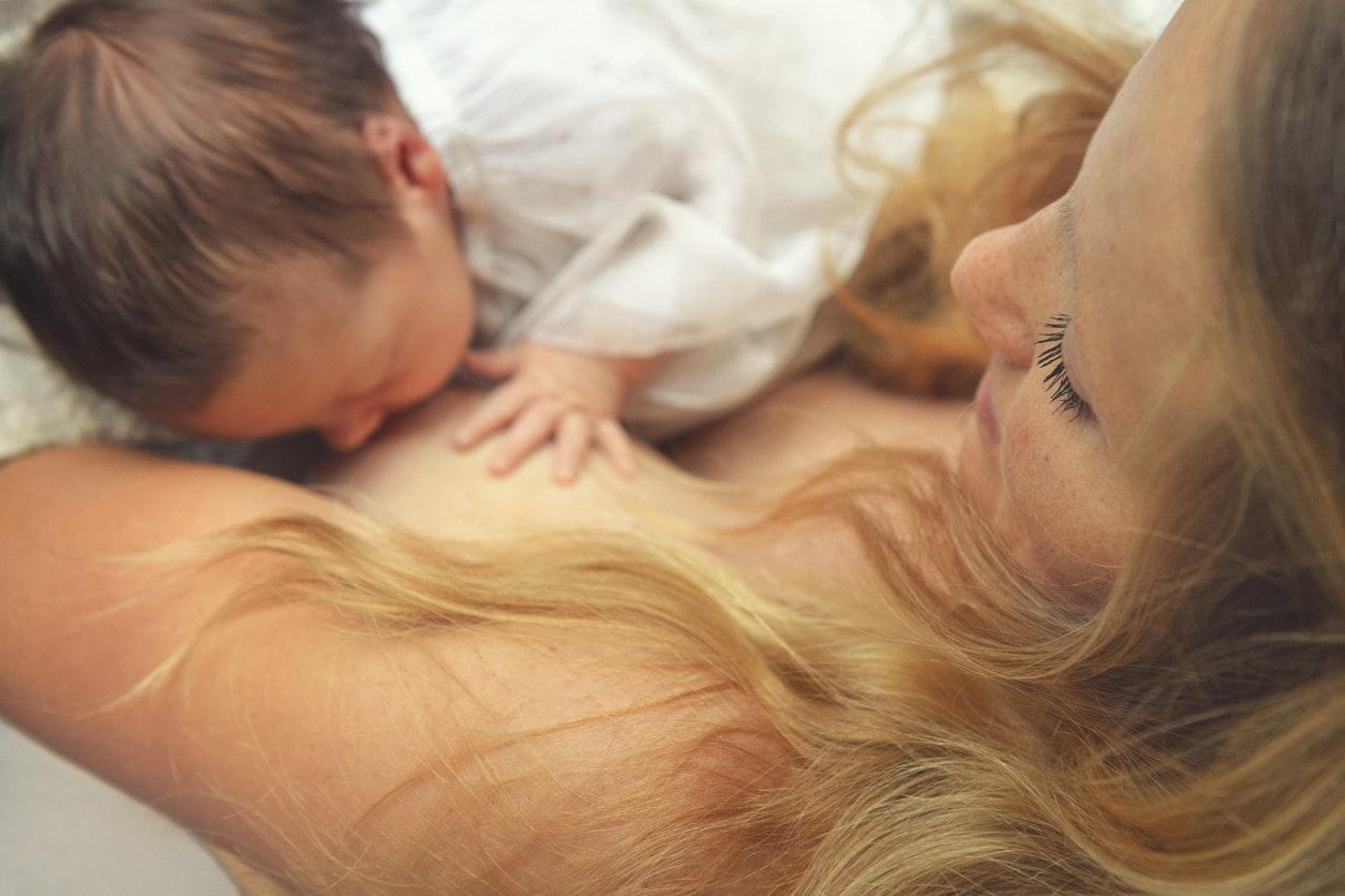 un bébé tète le sein de sa mère