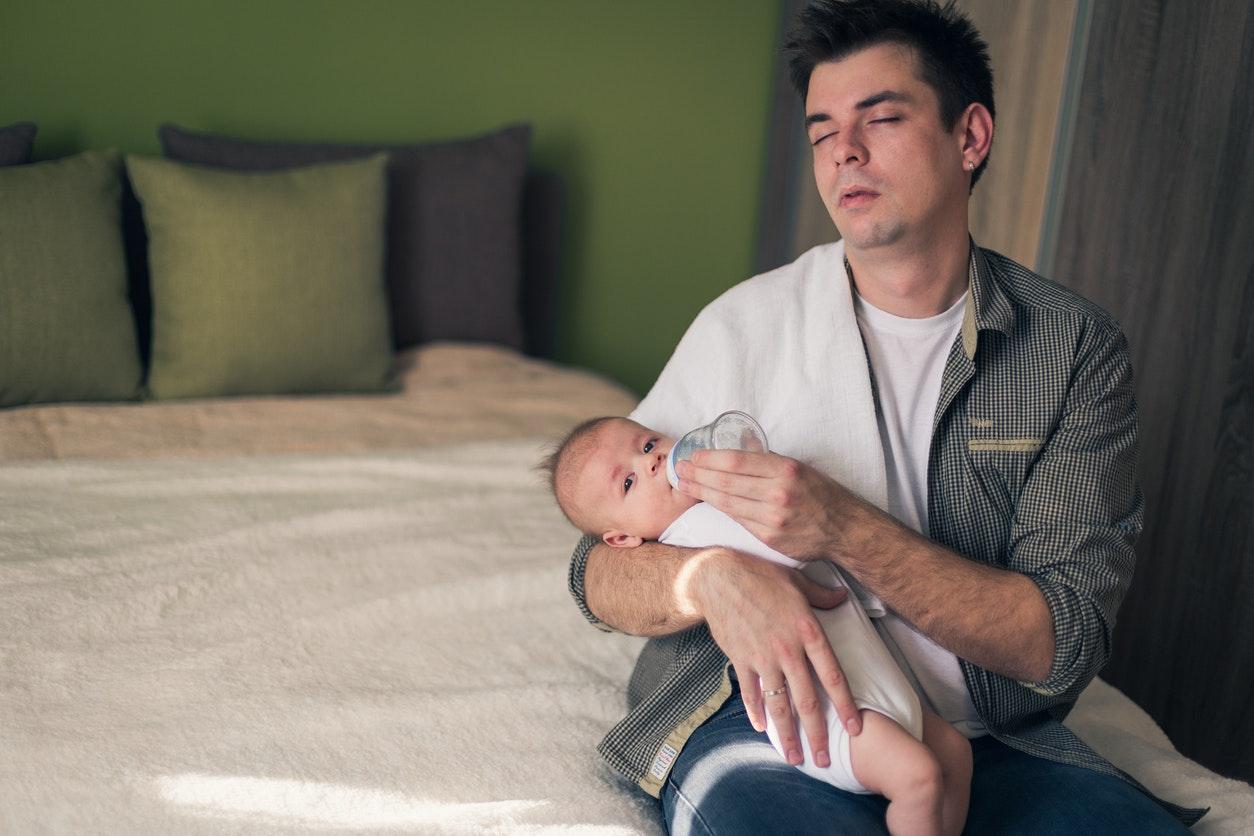 père donne biberon enfant