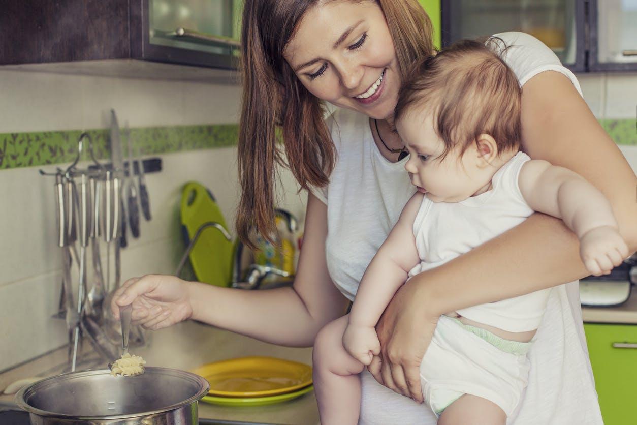 maman cuisine avec bébé dans les bras