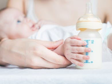 bébé tient son biberon