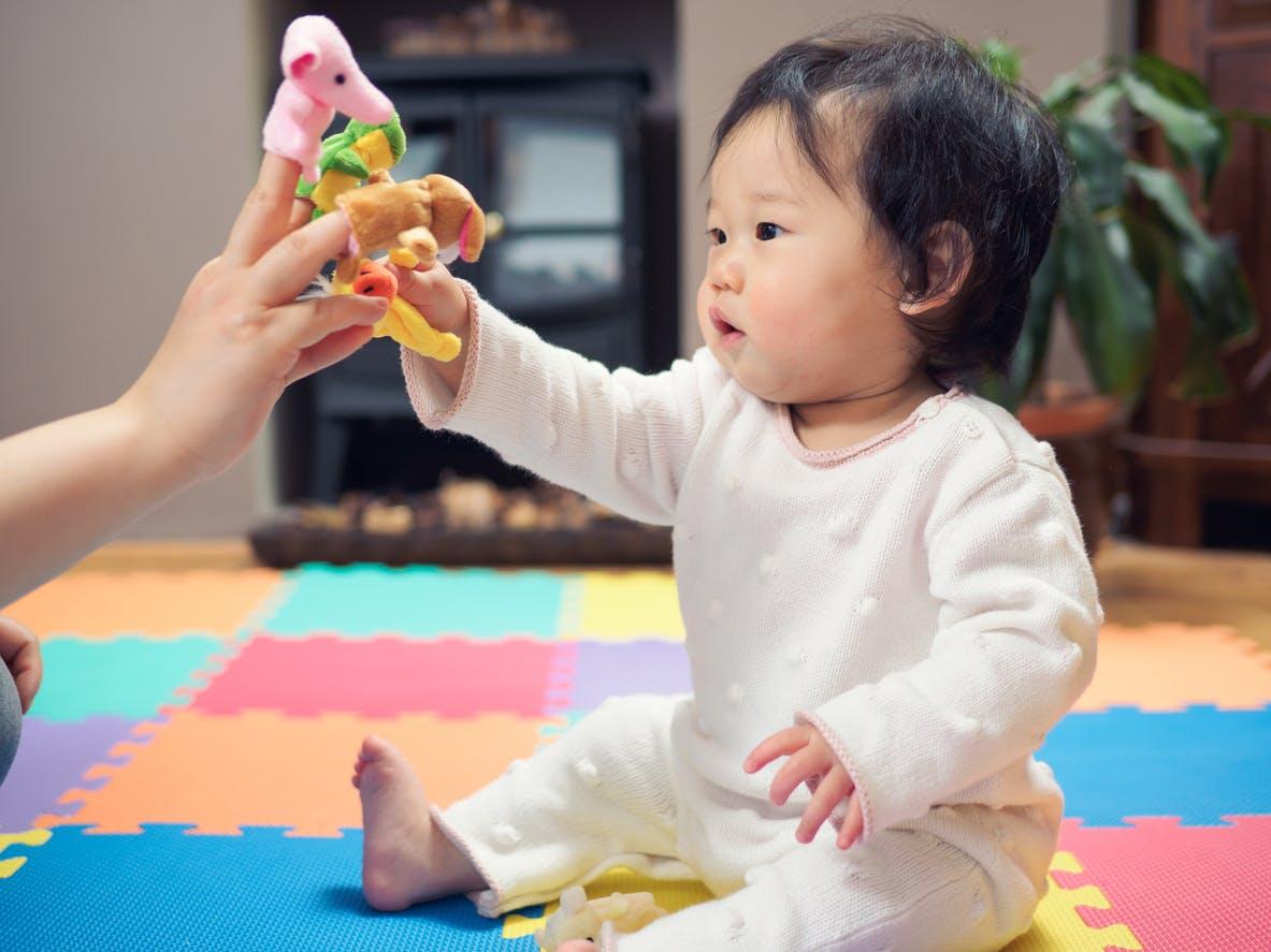 un bébé joue avec des marionnettes à doigts