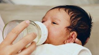 bébé et son biberon de verre