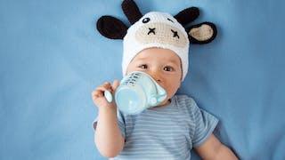 bébé boit dans une tasse d'apprentissage