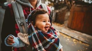 bébé souriant dans porte bébé