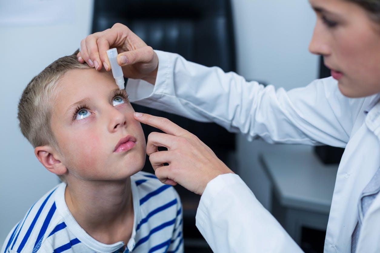 médecin mettant du collyre dans l'oeil d'un enfant