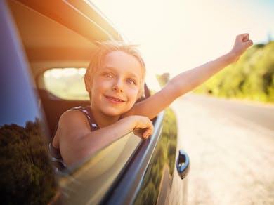 un enfant sort le bras de la voiture par la vitre ouverte