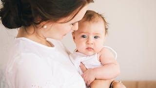 bébé  joli regard dans les bras de sa maman