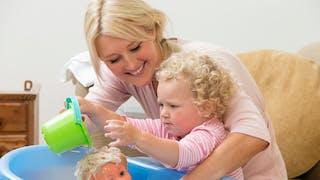 enfant fait prendre le bain à sa poupée