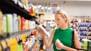 femme regarde étiquette cosmétiques