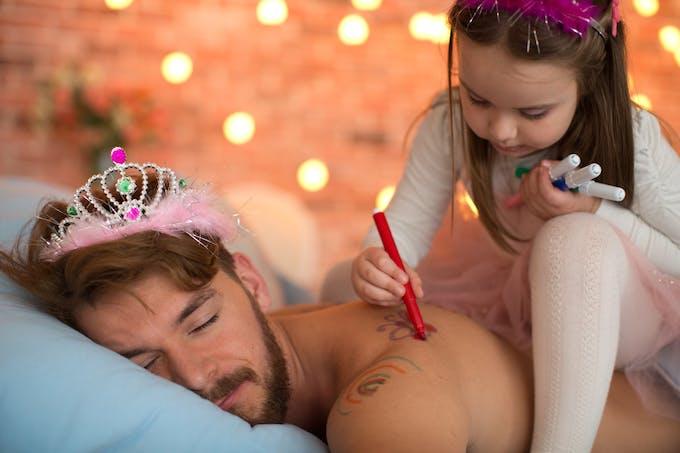 une petite fille dessine sur son père