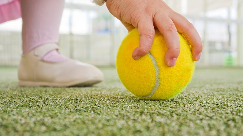 Un petit enfant ramasse une balle de tennis