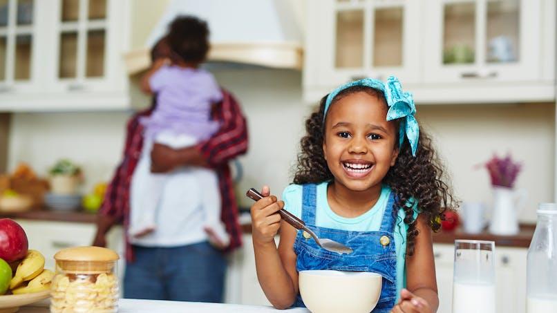 une petite fille mange des céréales