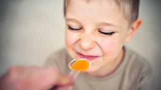 Petit garçon prenant une cuillerée d'antibiotiques