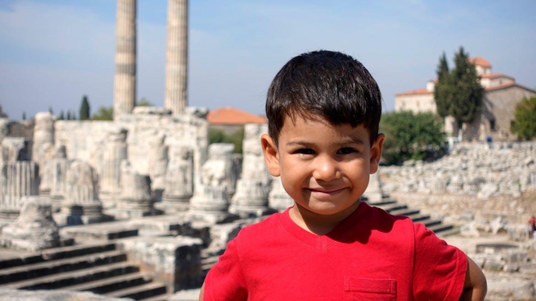 Un petit garçon tout sourire devant les ruines d'un temple en Grèce