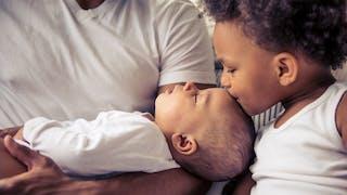 petite fille embrasse son frère nouveau-né
