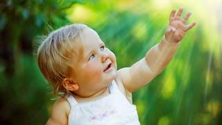 Un bébé blond se tourne vers le soleil