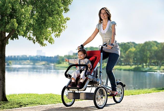 Maman qui se promène au parc avec bébé en vélo Taga.