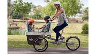 Maman qui pédale son vélo Taga avec deux enfants.