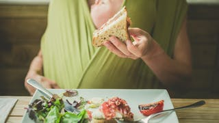 femme mange avec bébé en écharpe