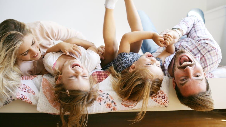 famille heureuse sur un lit
