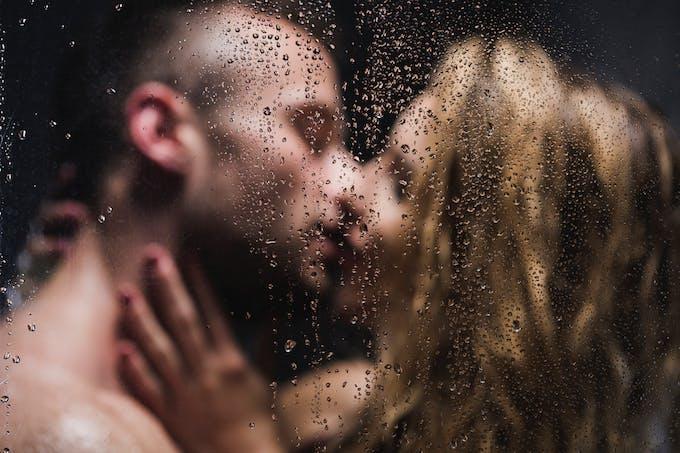 un couple s'embrasse derrière une vitre embuée