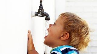 enfant buvant de l'eau à un robinet
