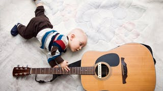 un bébé avec une guitare dans les mains