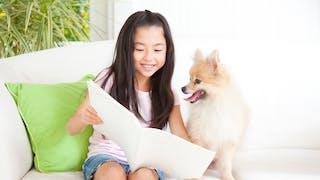 petite fille lisant et son chien