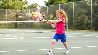 une petite qui joue au tennis