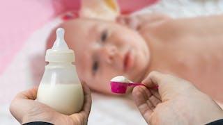 parent prépare un biberon de lait infantile