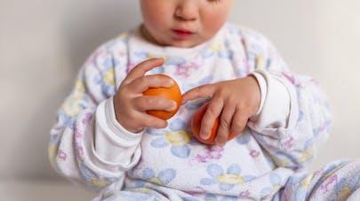 bébé avec oeufs dans les mains