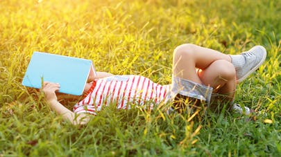 enfant dans l herbe un cahier sur la tête