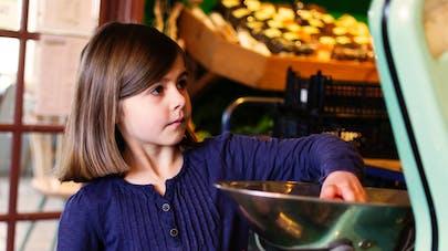 petite fille apprend à peser fruits