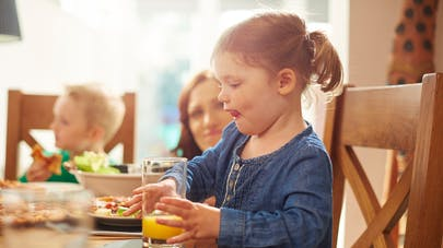 petite fille buvant un jus d'orange à table