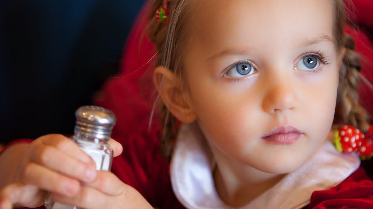 petite fille avec salière dans les mains