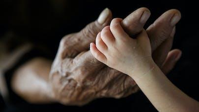 main de femme âgée et bébé