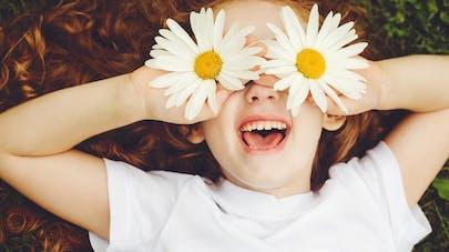 petite fille allongée des marguerites sur les yeux