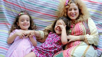 Une maman et ses deux fillettes allongées dans un lit