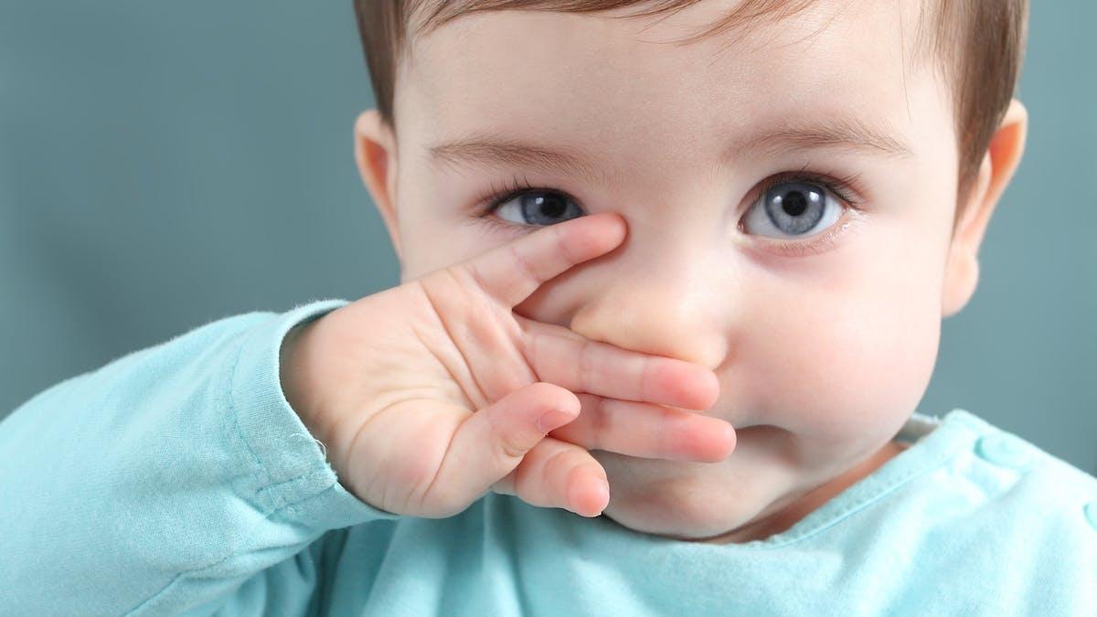 bébé touche son nez