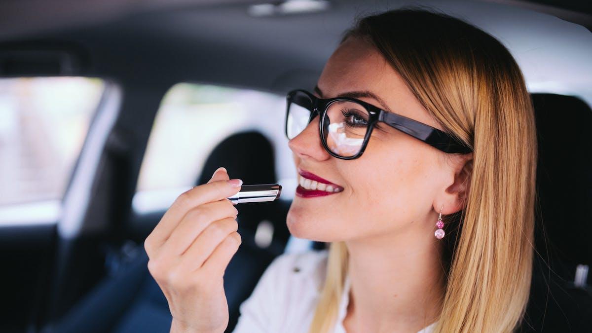 femme se maquille dans voiture