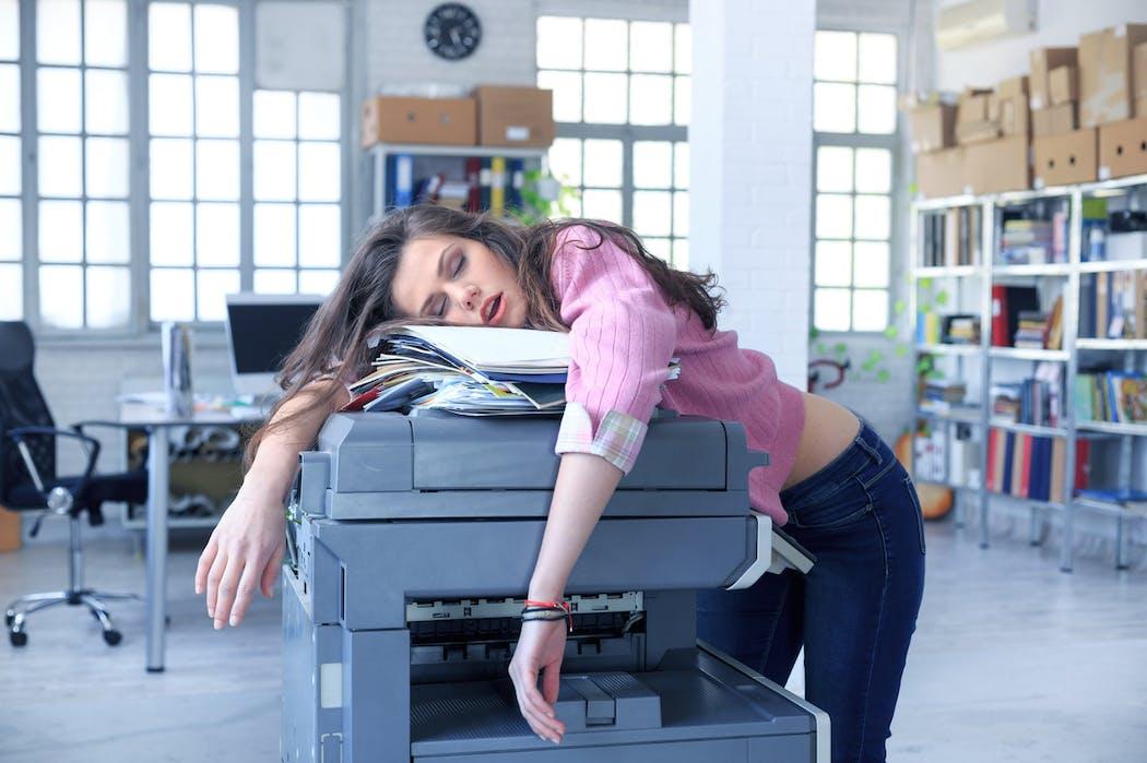 une femme épuisée écroulée sur une photocopieuse