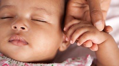 bébé endormi tenant main de sa maman
