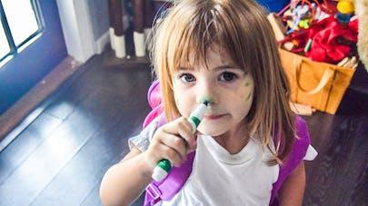 une petite fille se met du feutre sur le visage