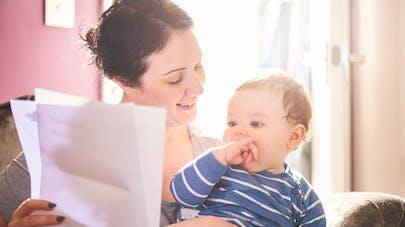 femme lit une lettre avec bébé sur les genoux