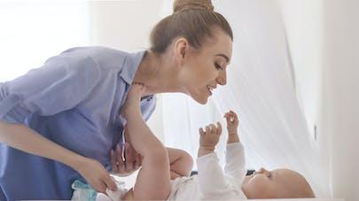 femme en change bébé sur table à langer